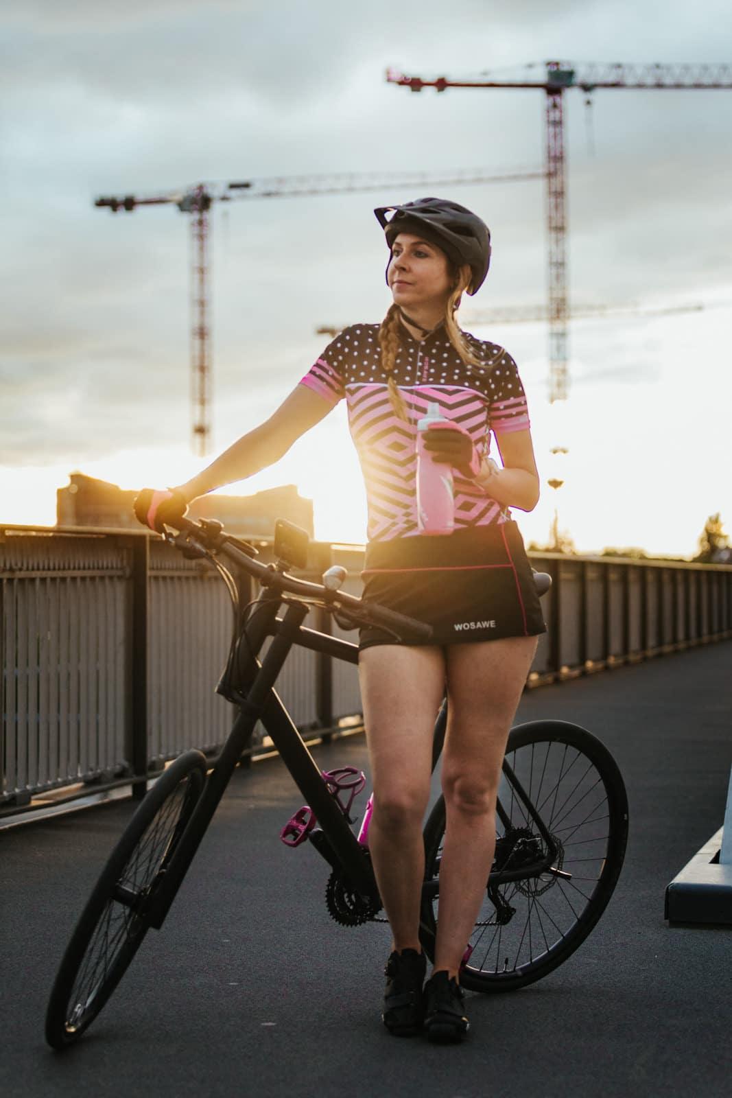 Frau steht mit pinken Radoberteil und Trinkflasche in Frankfurt angelehnt an ihr Cannondale Fahrrad