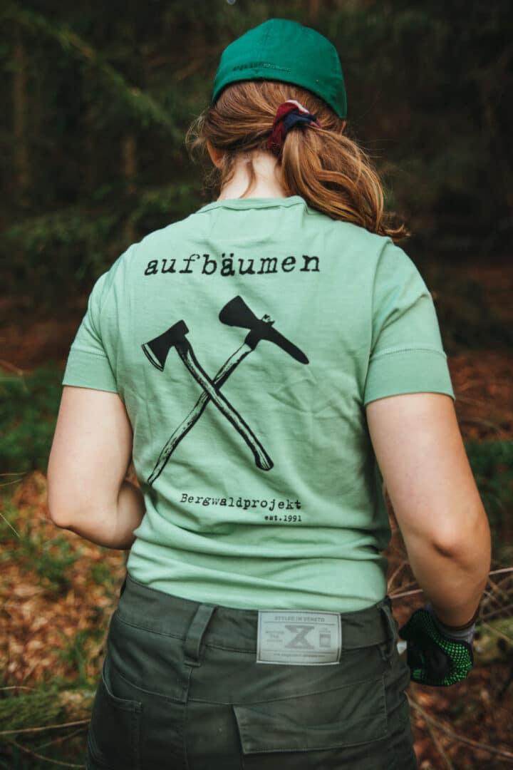 """Junge Frau mit Bergwaldprojekt T-Shirt in grün mit der Aufschrift """"aufbäumen"""" auf dem Rücken"""