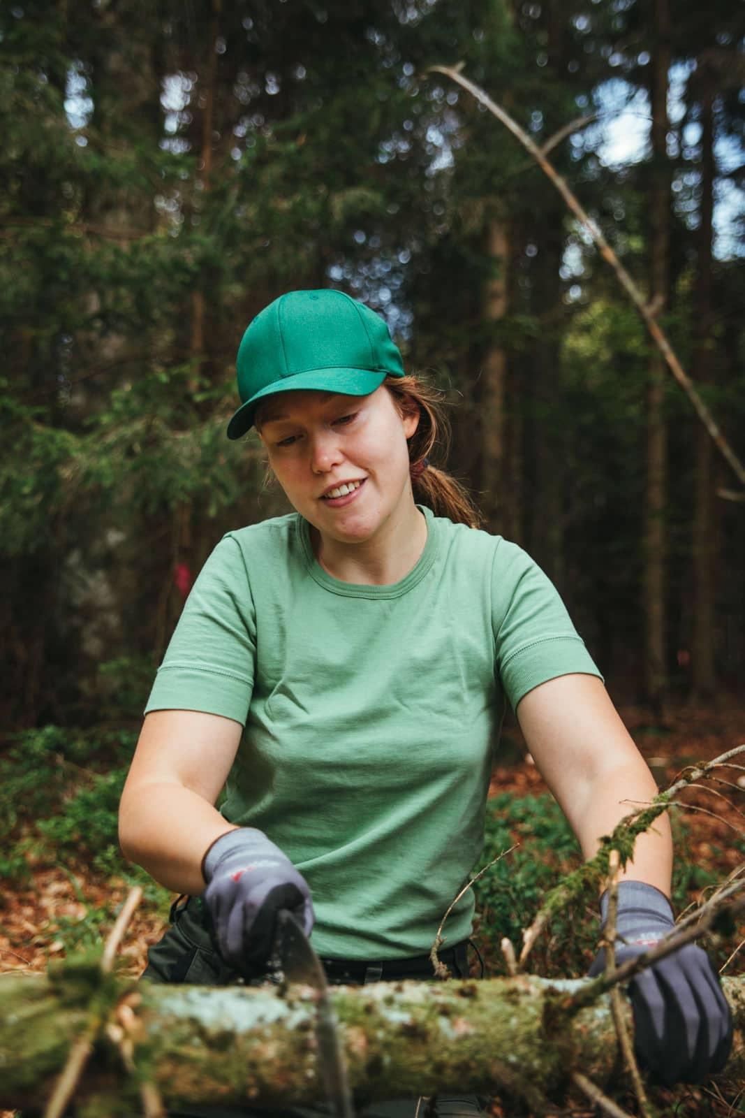 Frau sägt Äste an einem Baum ab