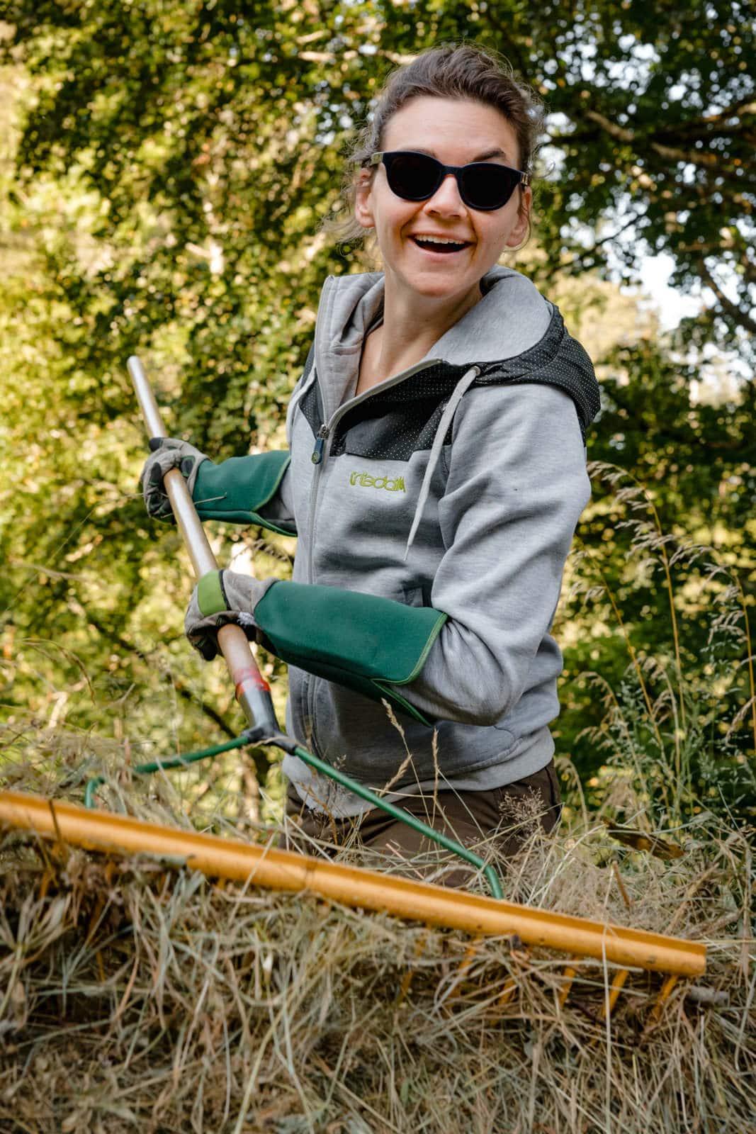 Frau recht Heu mit rechen auf einer Sommerwiese zusammen