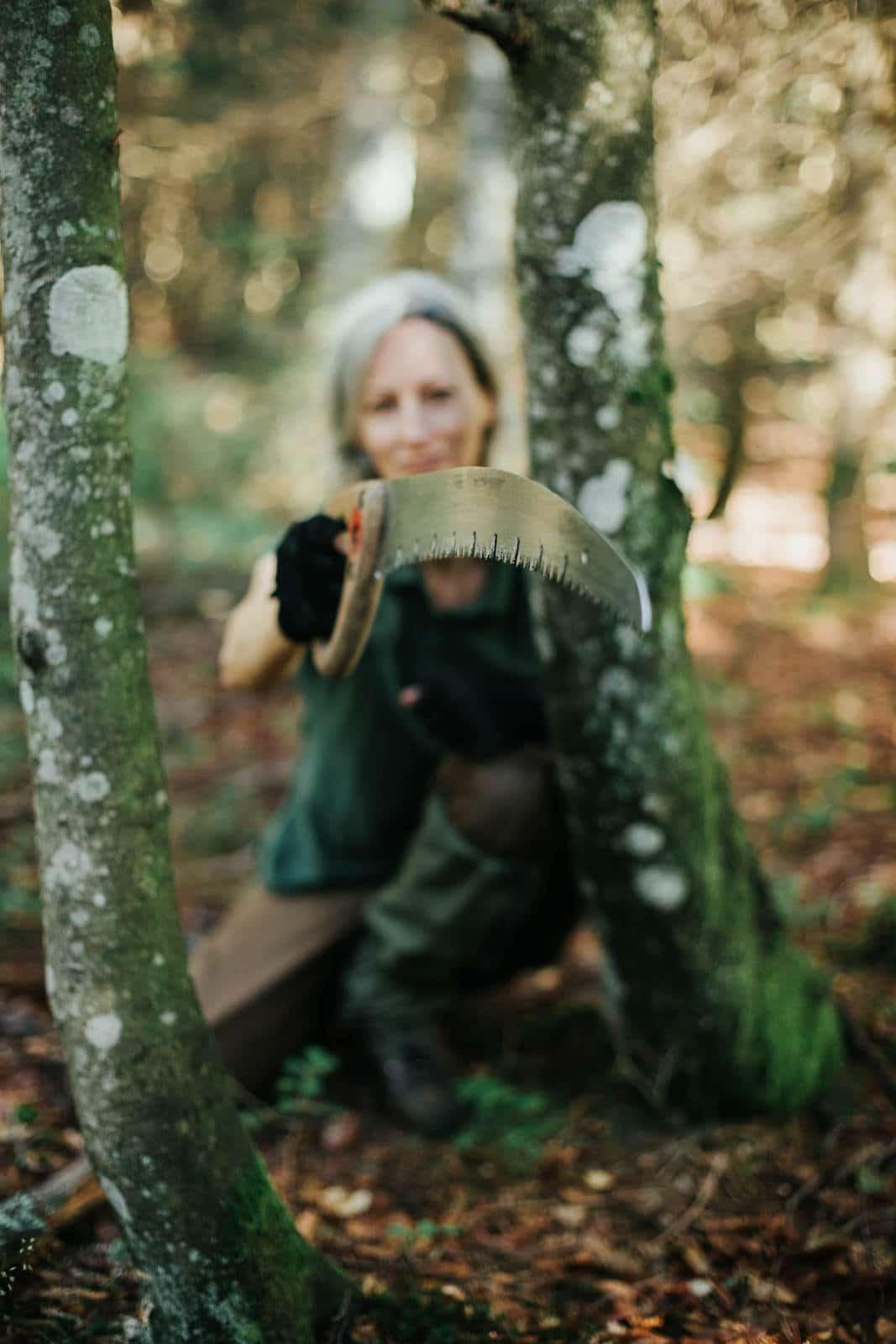 Frau zeigt Baumsäge in Kamera close