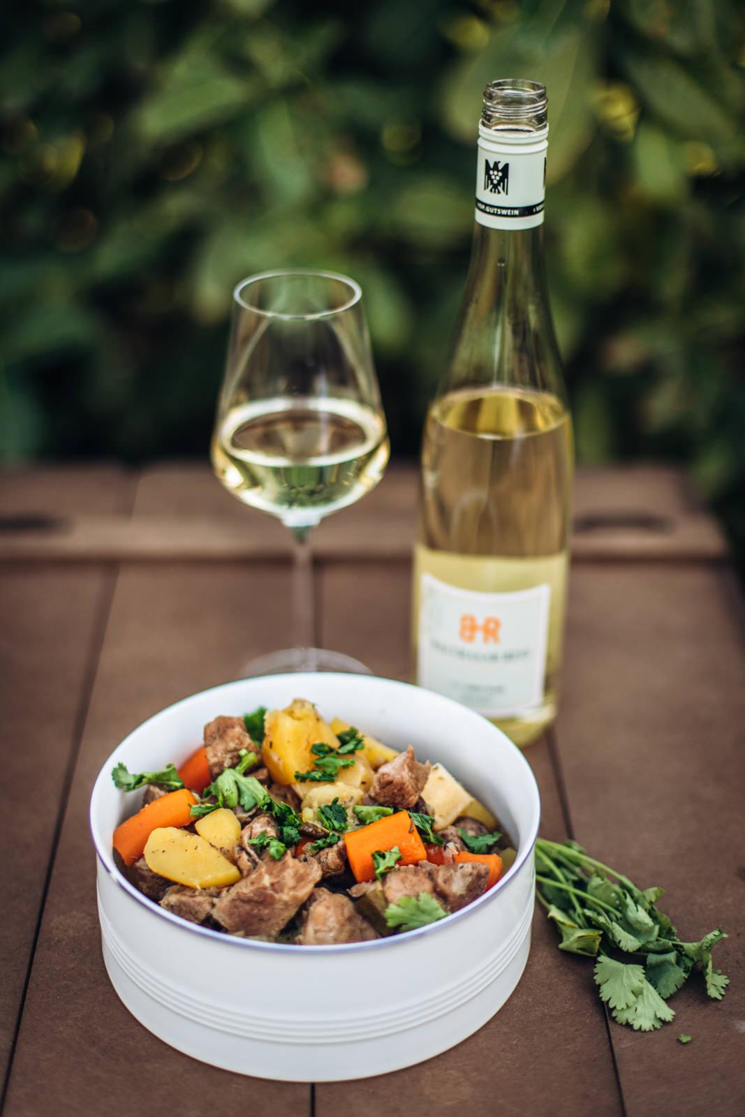 Fertiger Lamm Potjiekos mit einem Glas Weißwein