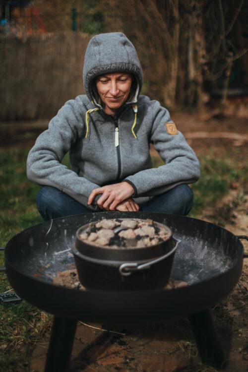 Eine Frau sitzt vor einem Dutch Oven und wartet auf das Essen