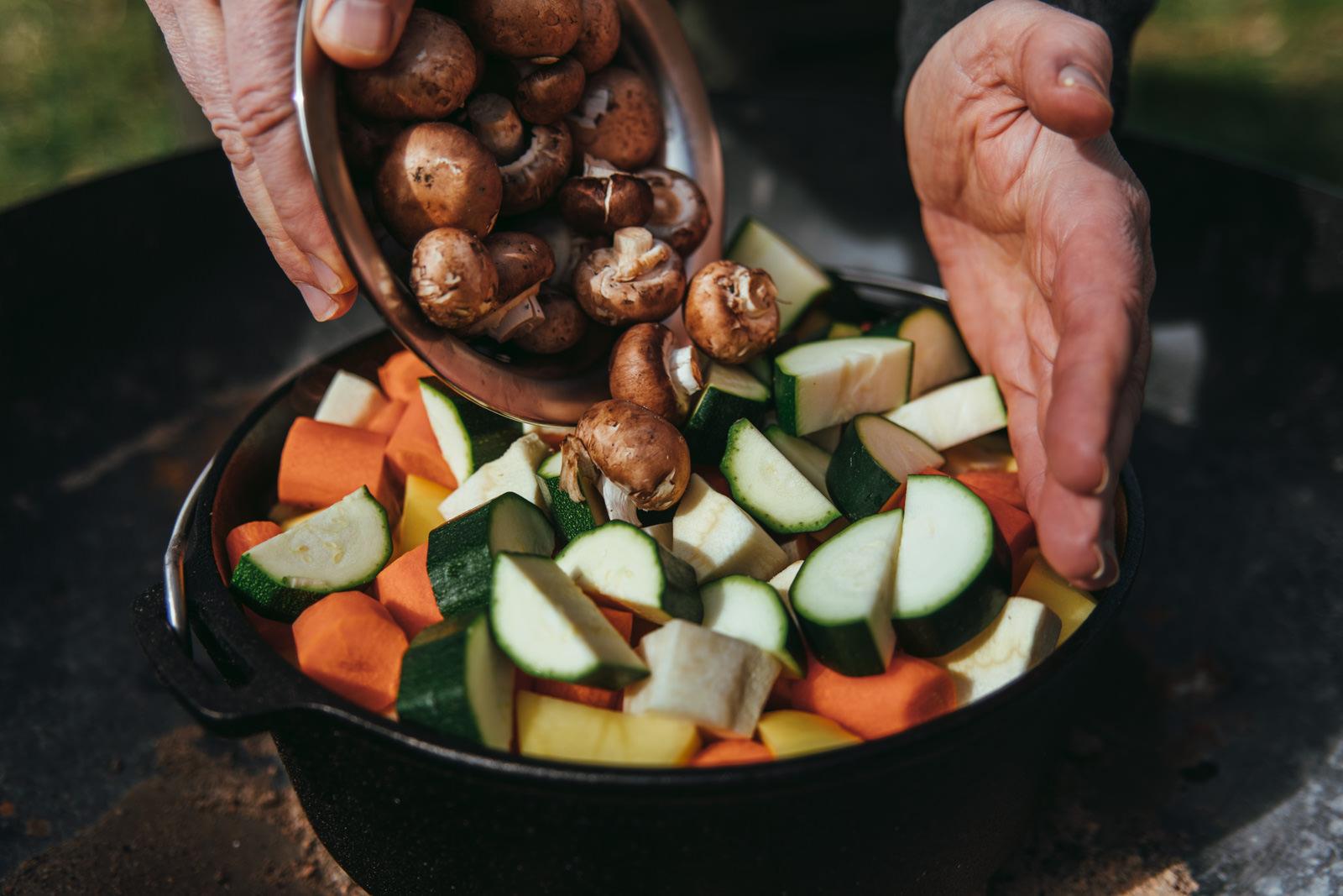 Champignons werden in einen Dutch Oven zugegeben.