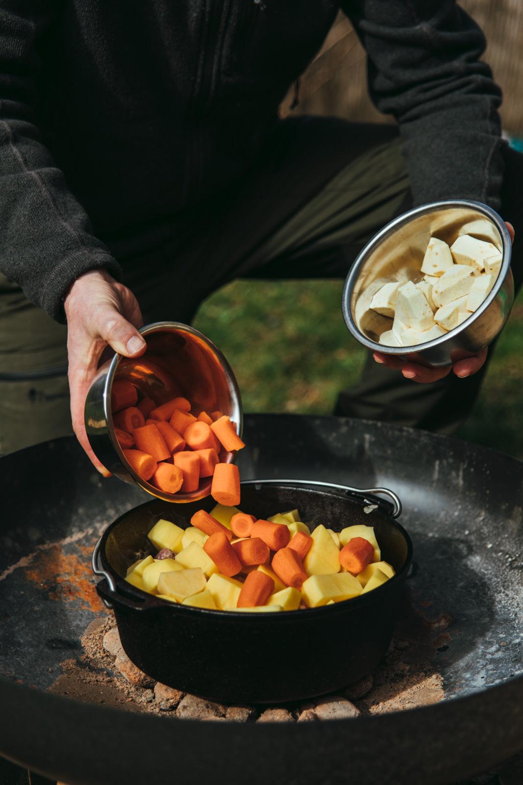 Karottten und Pastinake werden zu Kartoffeln in einen Dutch Oven geschüttet