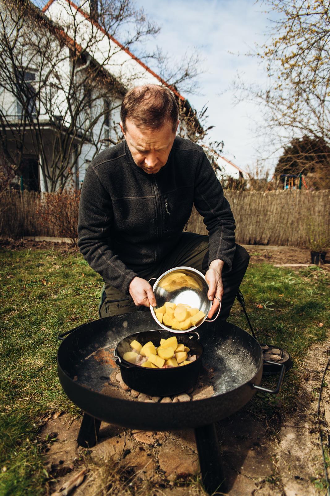 Ein Mann schüttet Kartoffeln in einen Gusseiserenen Topf