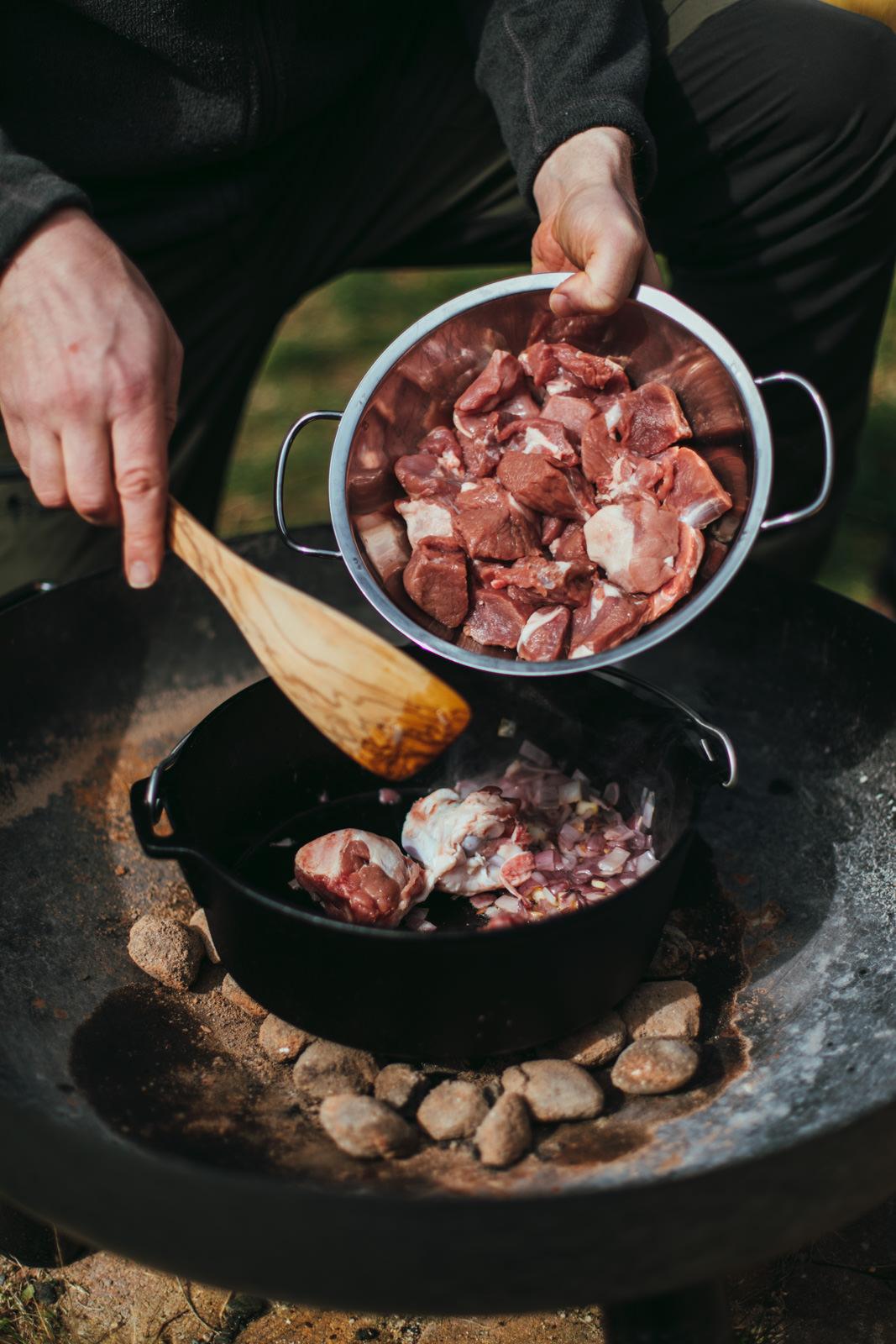 Lammfleisch wird in einen Gusseisernen Topf zugegeben.