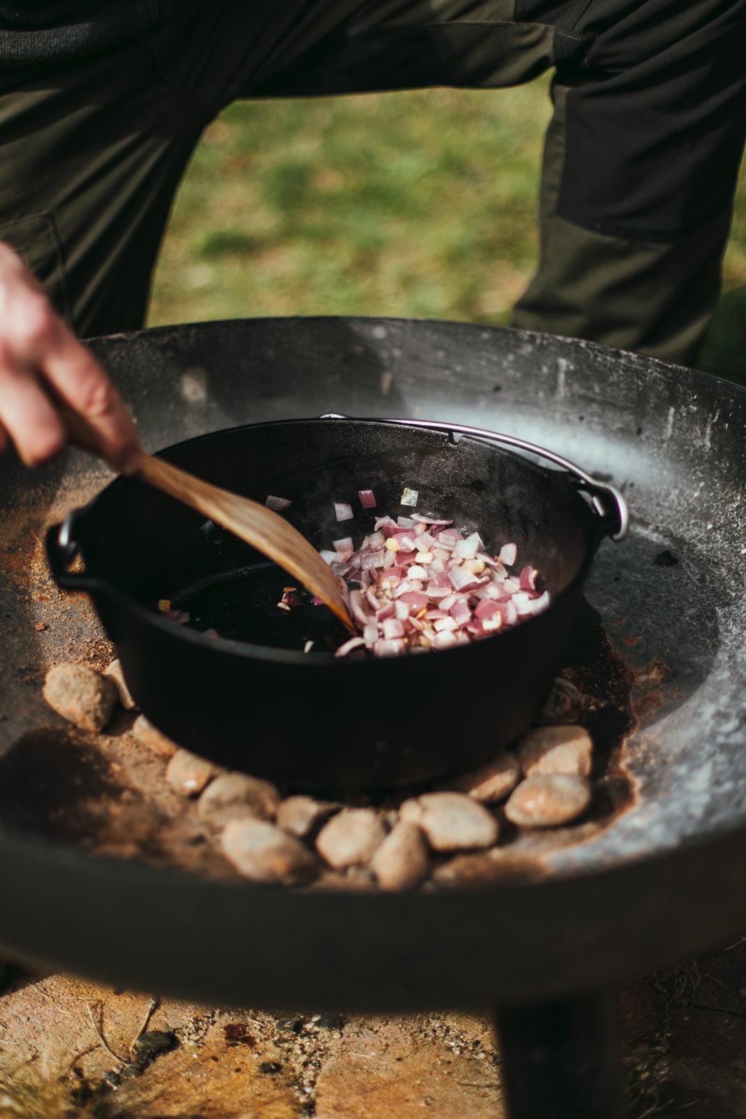 Zwiebeln werden im Gusseisernen Topf zur Seite geschoben