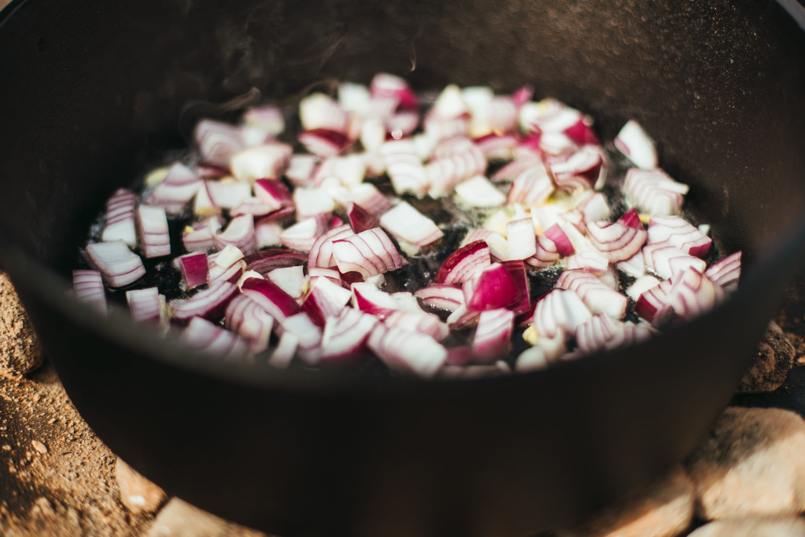 Zwiebeln braten in einem Gusseisernen Topf in Butter an.