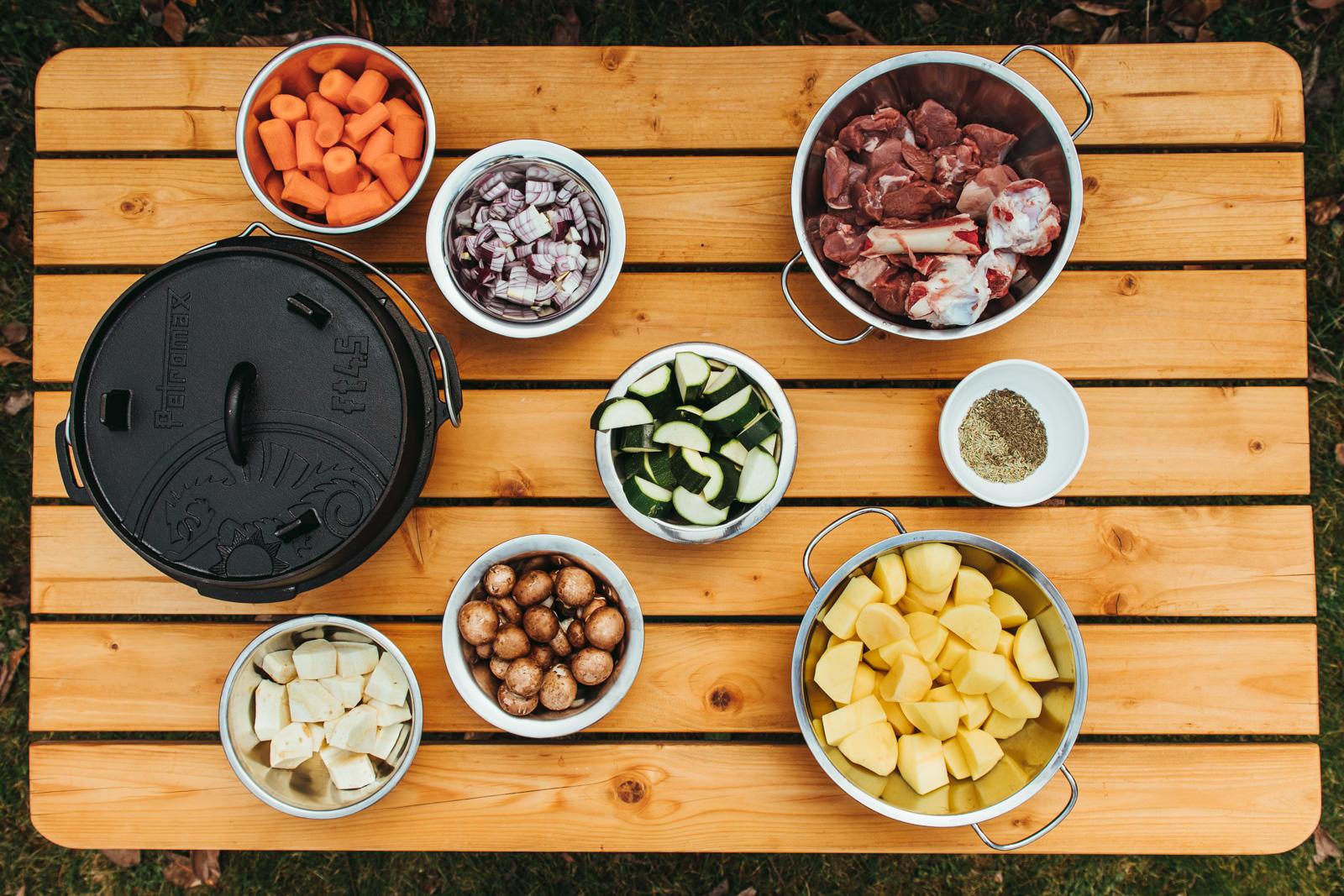 Ein Tisch voller Gemüse und Fleisch in Schalen angerichtet