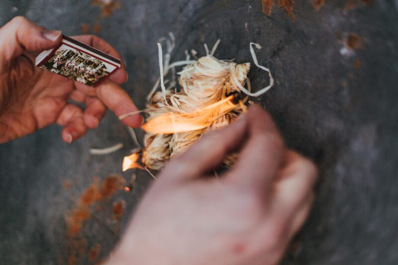 Eine Hand macht mit einem Streichholz Feuer an einer Holzwolle